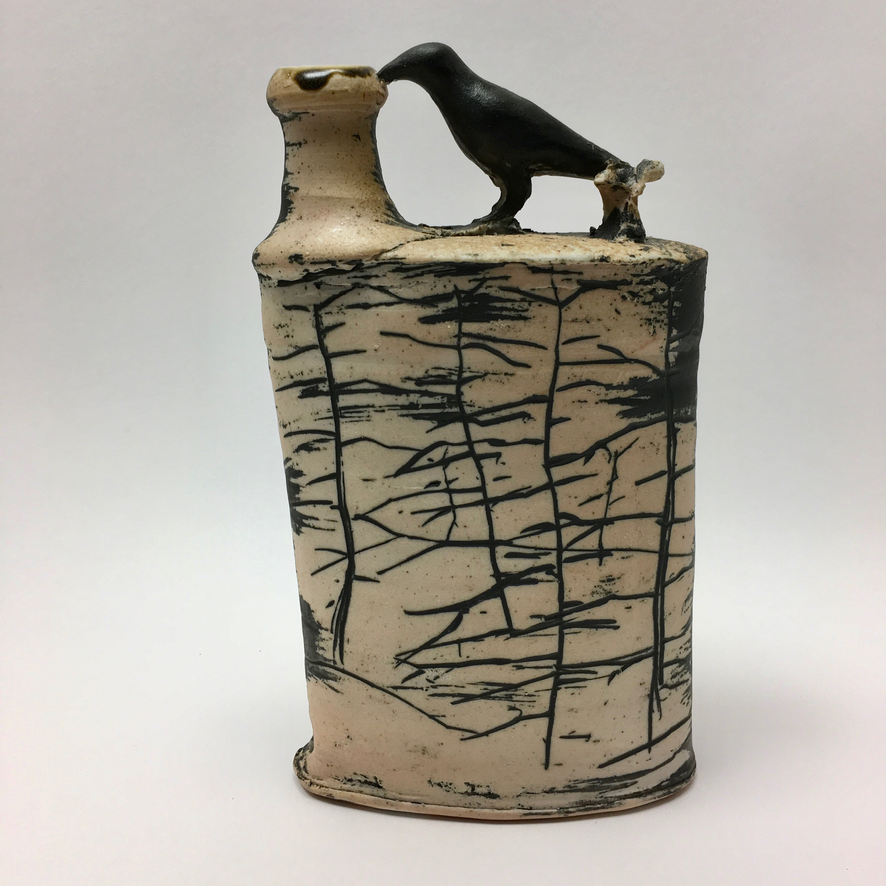 Wood fired flask by ceramic artist David Ernster. Fill with a beverage or enjoy as ornamental pottery. Black line tree design with a crow on top available at the Littelton League GAllery 81 MAin St Littelton NH