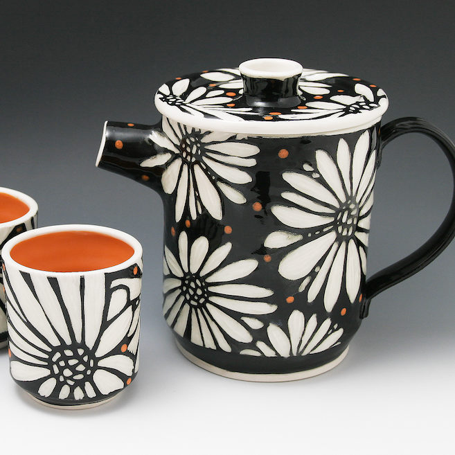 Ceramic teapot with floral daisy design by potter Melynn Allen is a delight. Handless tea cups to match. Bold design available at the Littleton League gift shop in teh White Mountains of NH