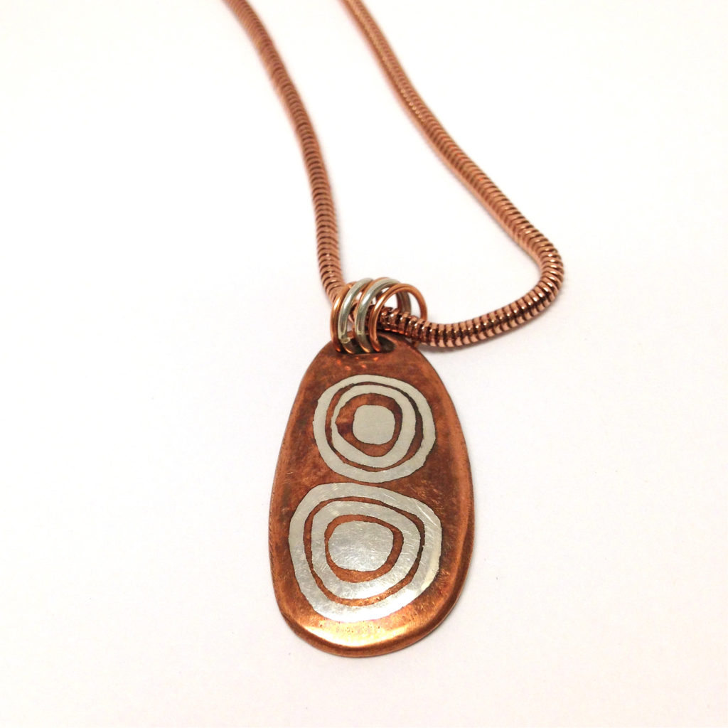 Necklace made øo copper and silver with a circle design. fine craft jewelry at the Littleton Leagu´of NH Craftsmen Gallery located on Main St. Many other jewelry by Michela available at the shop with unusual gifts.